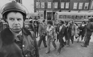 Photo of a law enforcement officer in front of school buses arriving at South Boston High School, Jan. 8, 1975.